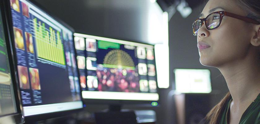 A woman looking at 2 computer monitors