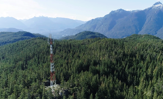 A network tower in the middle of forests and a mountain