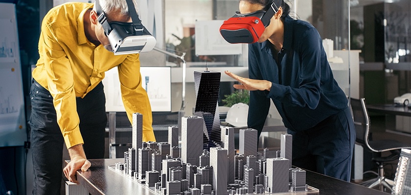 Two people using a VR headset and looking at a 3D city
