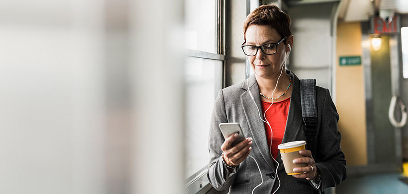 A woman looking at her phone holding a coffee cup and wearing earphones