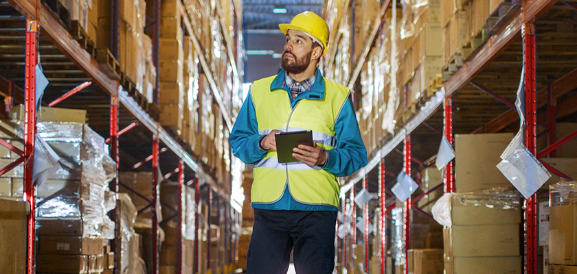 A construction man holding a tablet looking at shipment