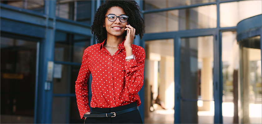 A woman in a polka dot shirt on her phone
