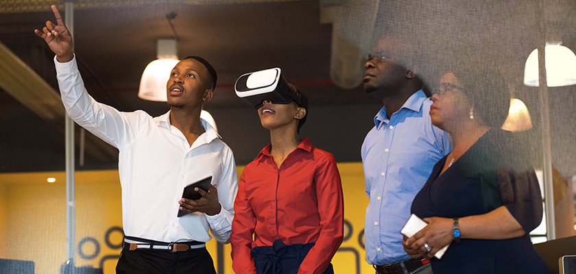 A woman wearing a VR headset while people stand around her