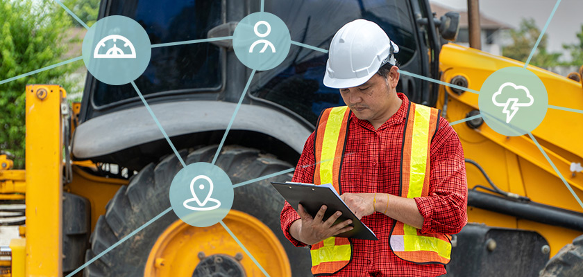 Foreman using tablet with fleet construction vehicle
