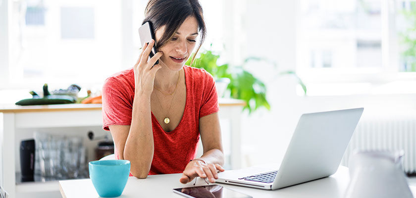 Woman on cell phone with laptop open at home