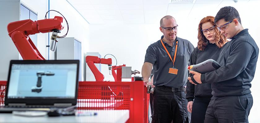 Trois personnes inspectent un bras robotique
