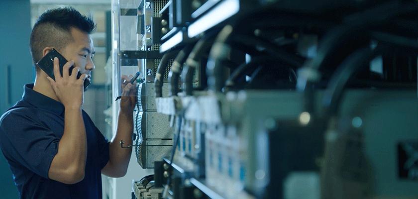 Un homme parlant au téléphone inspecte de la machinerie