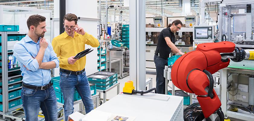 Deux hommes parlent pendant qu'un autre travaille avec la machinerie