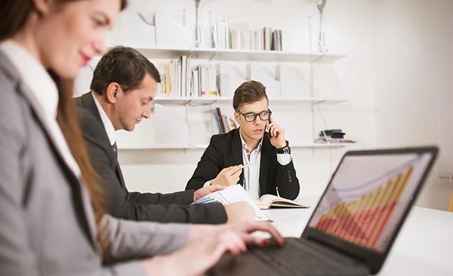 Un homme parle au téléphone, une femme travaille sur un ordinateur portable et un autre homme lit des papiers