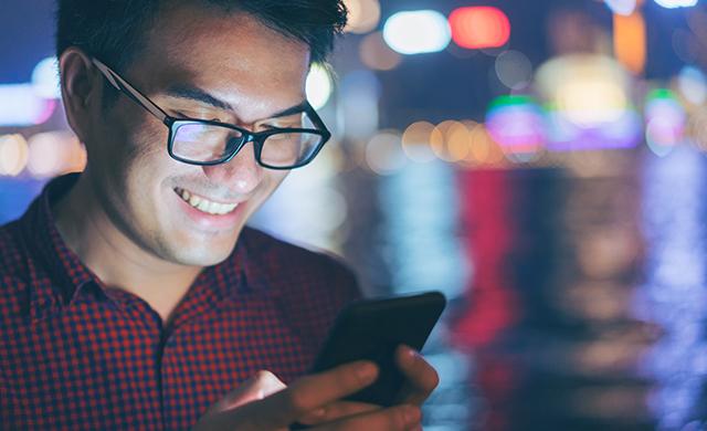 Un homme souriant utilise son téléphone cellulaire