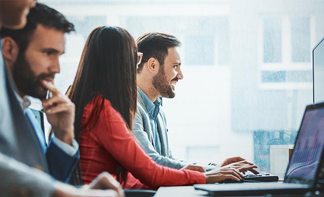 Trois personnes travaillent sur leurs ordinateurs portables