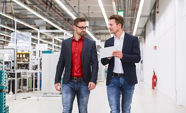 Deux hommes marchent en regardant une tablette