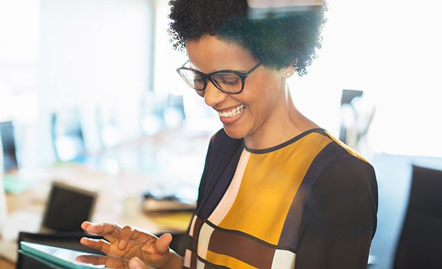 Une femme riant utilise une tablette
