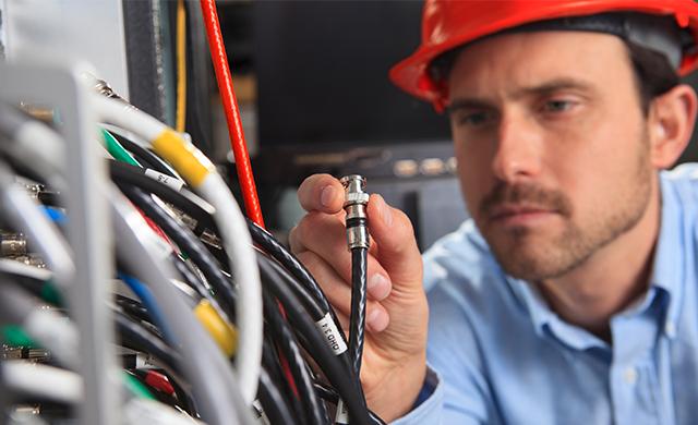 Un homme portant un casque rouge inspecte des fils