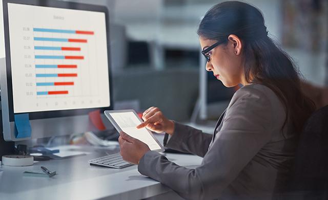 Une femme qui s'assoit devant l'écran d'un ordinateur utilise une tablette