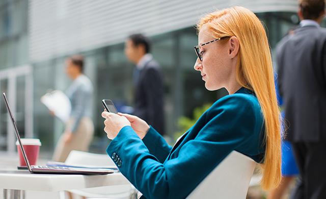Une femme s'assoit à une table dehors et utilise son téléphone cellulaire
