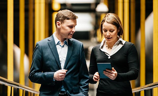 Une homme et une femme marchent en regardant une tablette