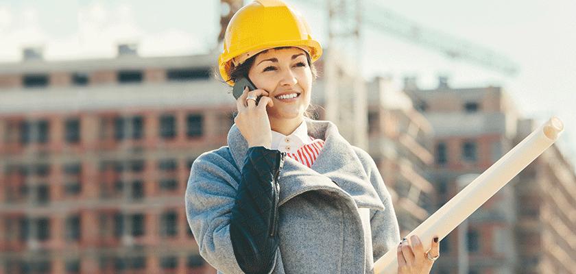 Une femme portant un casque de construction parle à la téléphone