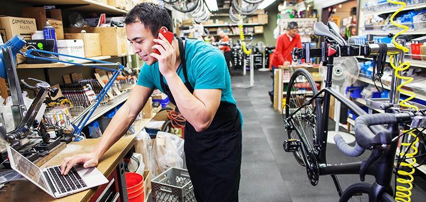 Un homme utilise son téléphone cellulaire et ordinateur portable dans un atelier de réparation de vélos