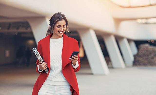 Une femme portant un manteau rouge et tenant un cahier regarde son téléphone cellulaire