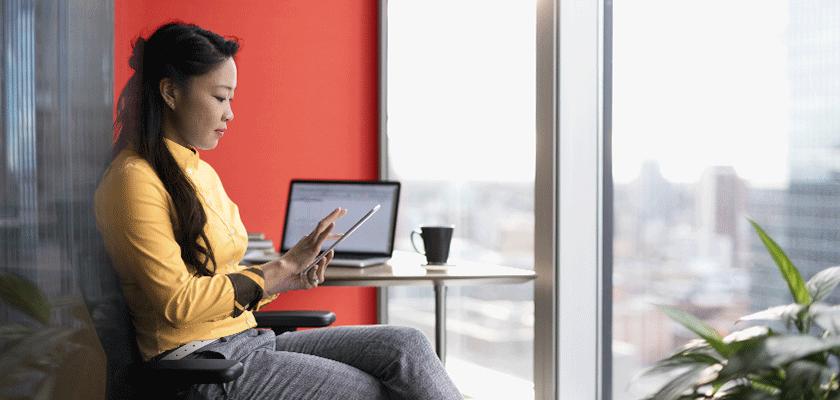 Une femme qui s'assoit et utilise une tablette