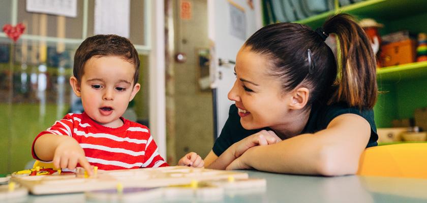 Adulte interagissant avec un enfant heureux dans un espace sécurisant