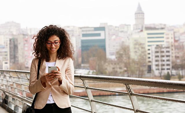 Une femme regardent l'écran d'un téléphone cellulaire sur un pont dans une ville