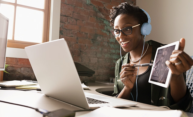 Une femme portant des écouteurs présente une tablette à un ordinateur portable