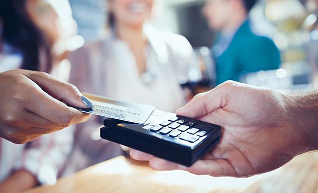 Une femme tapote sa carte de crédit sur une machine de débit