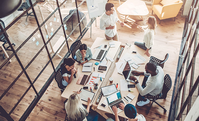 Une vue aérienne d'un groupe de personnes avec des appareils électroniques travaillant autour d'un table