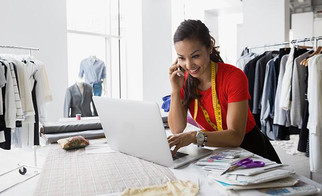 Une femme parlant à la téléphone utilise un ordinateur portable