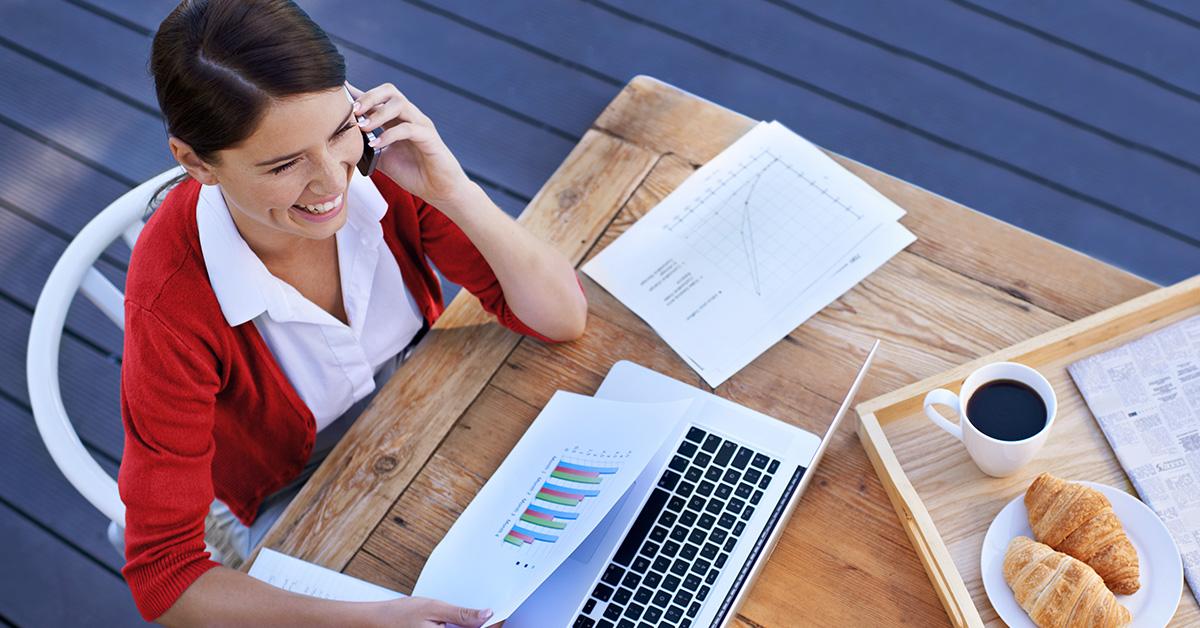 Une femme parlant au téléphone travaille sur un ordinateur portable