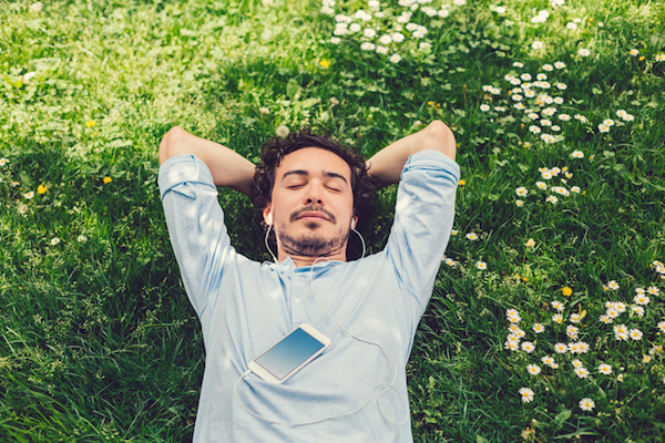 Man relaxing in a field of grass and flowers.