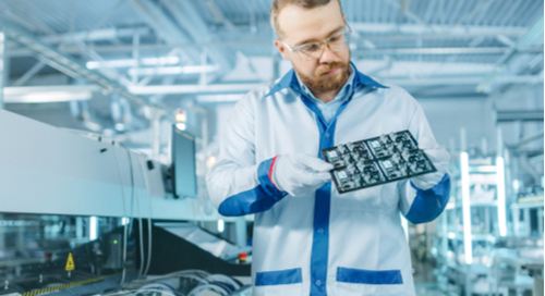 Man in a labcoat examines printed circuit board for manufacturing testing
