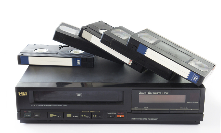Several VHS tapes stacked over a VHS player