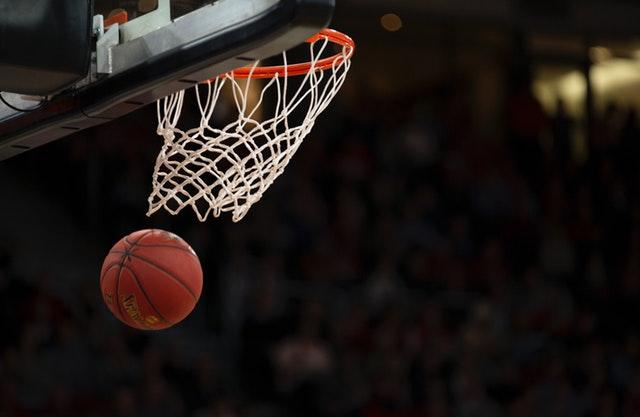 A basketball falls through a net
