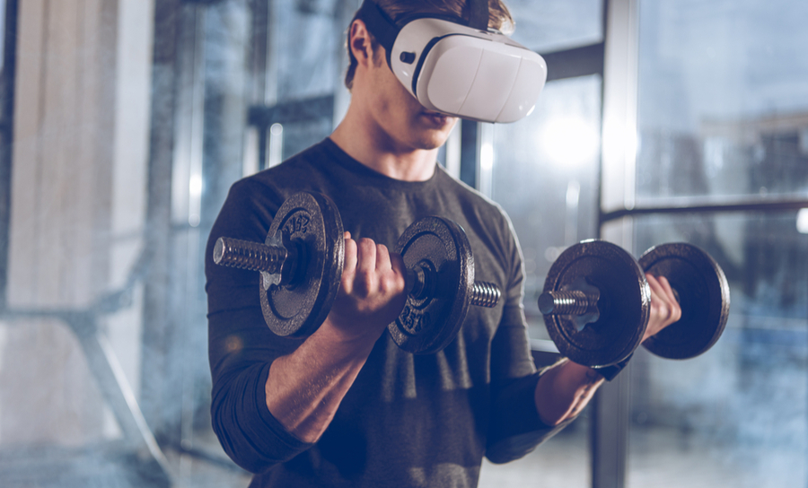 Man wearing virtual reality headset while lifting weights