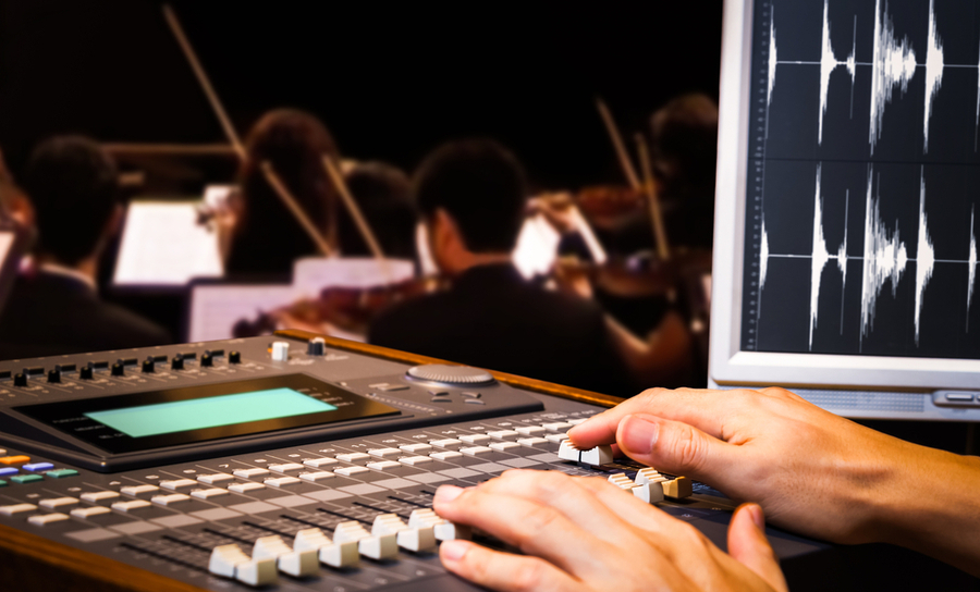 A sound engineer recording orchestra music to highlight a movie