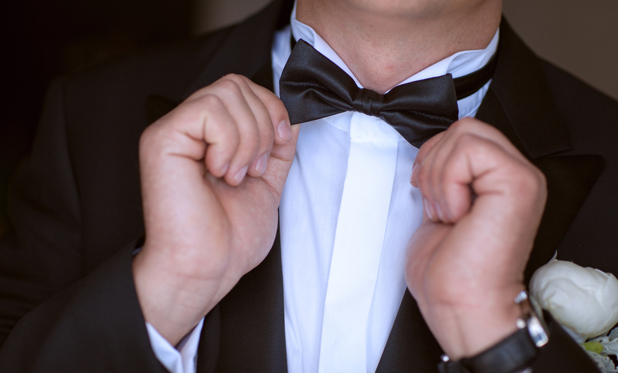 Person wearing tuxedo while righting a bow-tie