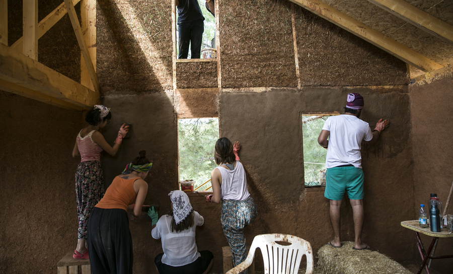 Group of active people earth plastering a home