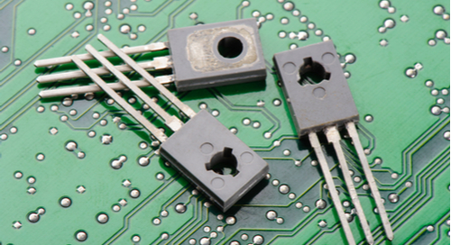 Picture of three transistors overlaid on a green circuit board