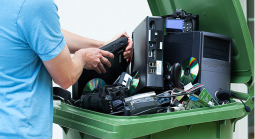 Man trying to stuff electronics into a green recycling bin