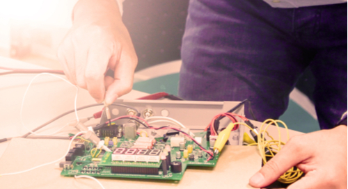 Person testing a circuit board on a desk