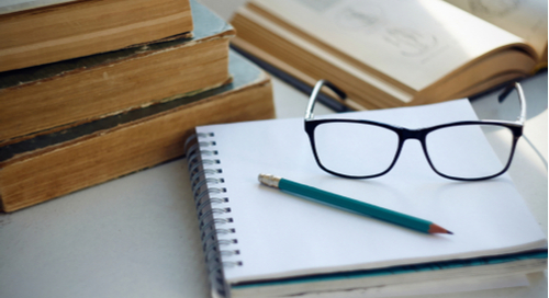 Book stack and notebook with a pencil and glasses on top