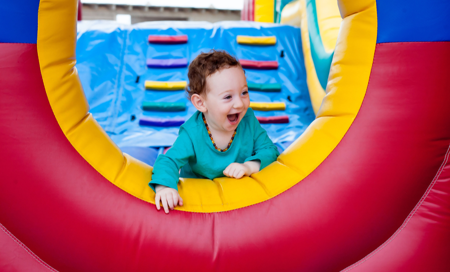 A child in a bounce house making a lot of noise having fun