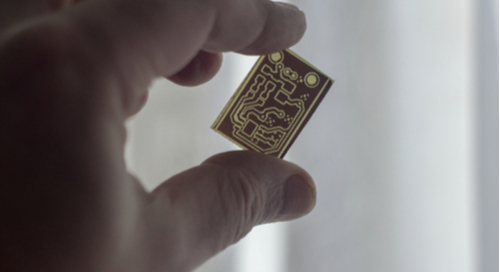 Small circuit board held between fingers