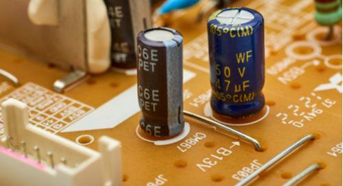 Capacitors and resistors on an orange circuit board