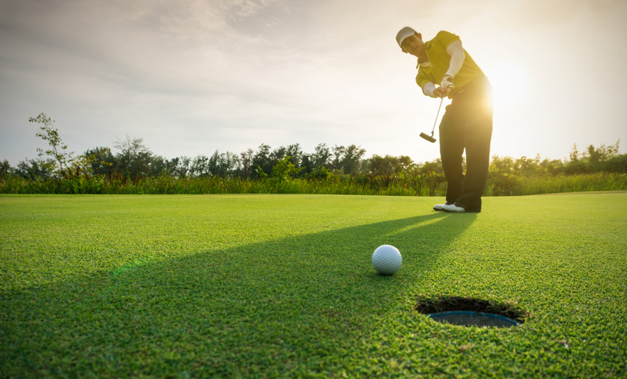 Man putting a golf ball on green grass