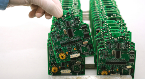 Gloved hand picking up a circuit board in a row of manufactured printed circuit boards