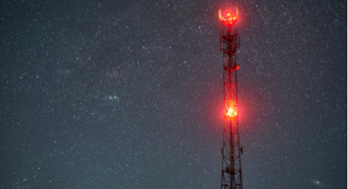 Radio tower glowing red against the starry night sky